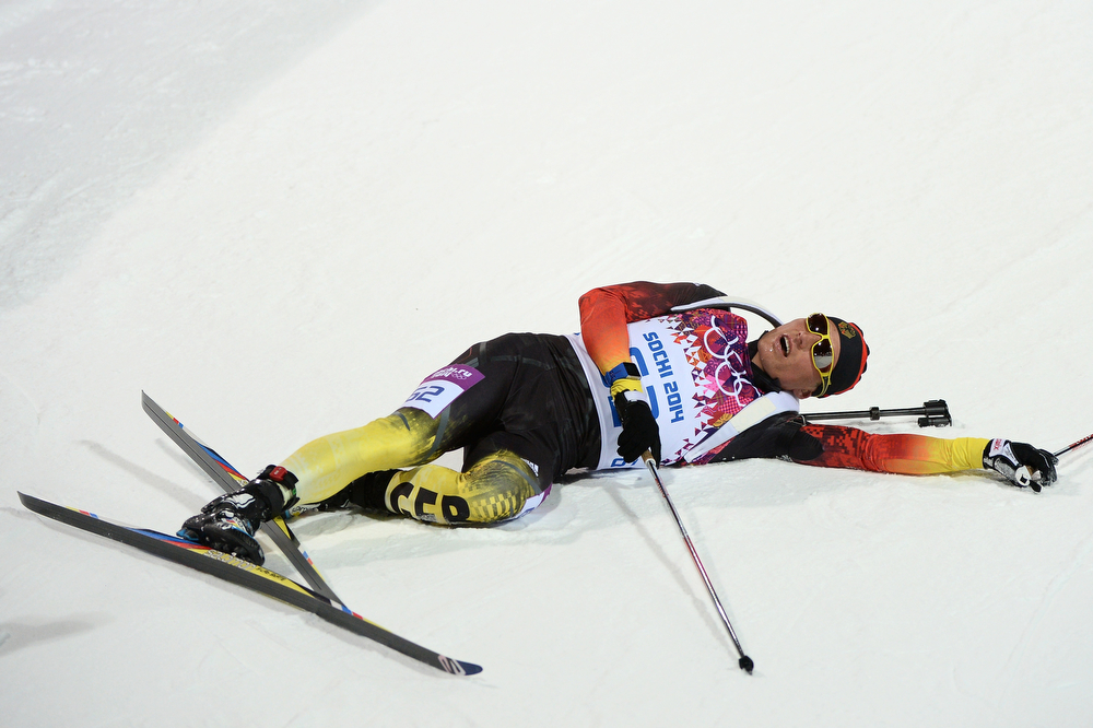 . Simon Schempp of Germany lies on the ground after crossing the finish line in the Men\'s Sprint 10 km during day one of the Sochi 2014 Winter Olympics at Laura Cross-country Ski & Biathlon Center on February 8, 2014 in Sochi, Russia.  (Photo by Harry How/Getty Images)