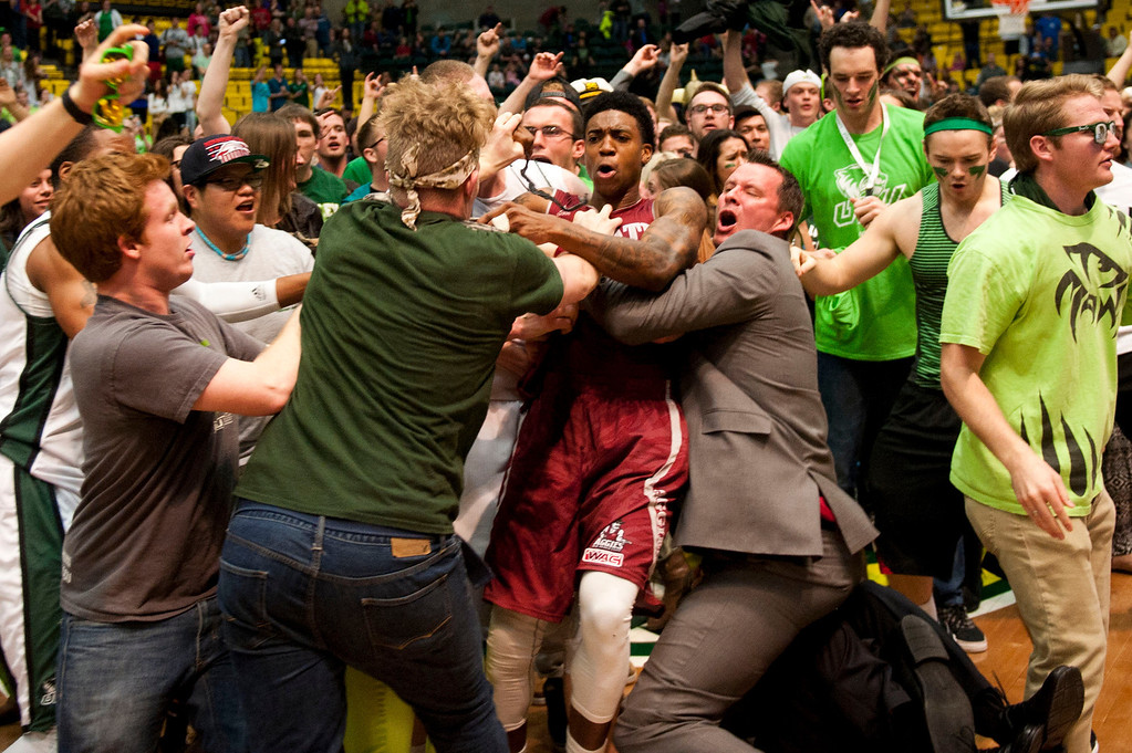 . In this Thursday, Feb. 27, 2014 photo, New Mexico State\'s Daniel Mullings, at center in red and white jersey, is involved in a brawl involving players and fans who came onto the court when New Mexico State guard K.C. Ross-Miller hurled the ball at Utah Valley\'s Holton Hunsaker seconds after the Wolverines\' 66-61 overtime victory against the Aggies on Thursday night. Feb. 27, 2014.  (AP Photo/The Daily Herald, Grant Hindsley)