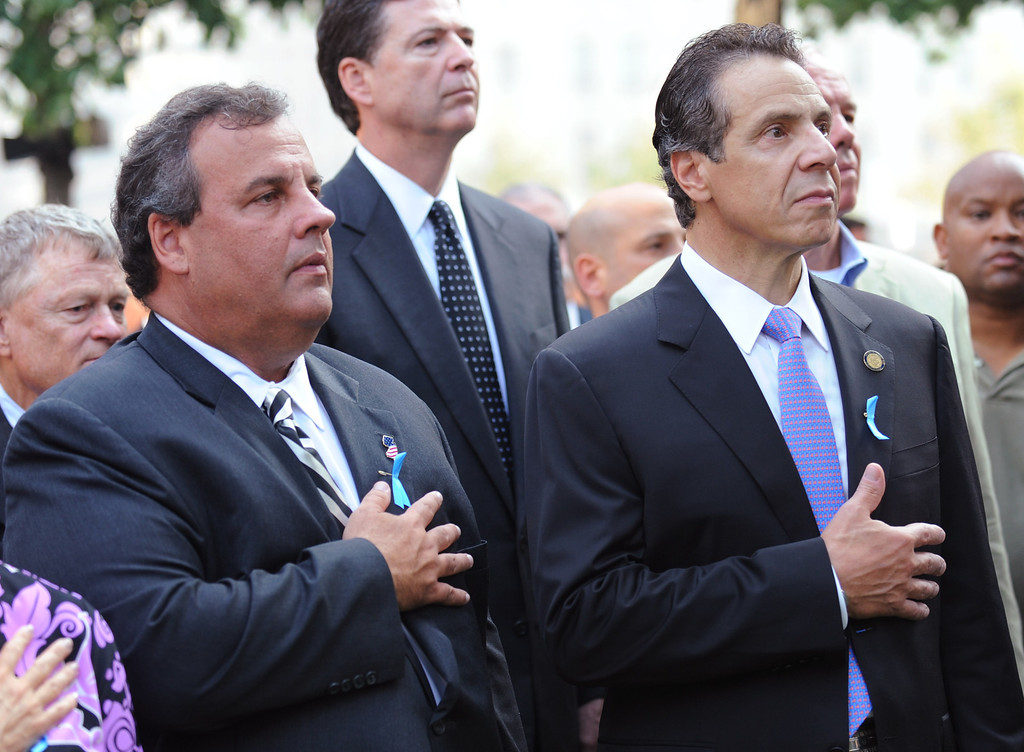 . New Jersey Gov. Chris Christie (L) and New York Gov. Andrew Cuomo (R) hold their hands over thier hearts at the 9/11 Memorial during ceremonies for the twelfth anniversary of the terrorist attacks on lower Manhattan at the World Trade Center site on September 11, 2013 in New York City.  (Photo by David Handschuh-Pool/Getty Images)