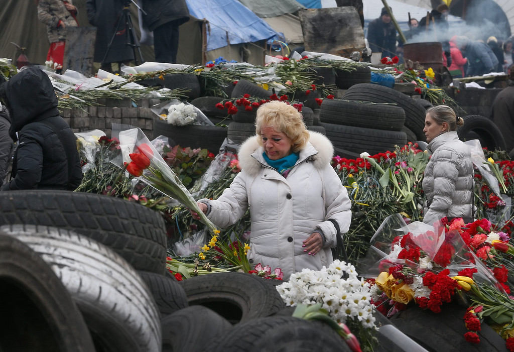 . Ukrainians gather near piles of flowers and candles as they remember those killed during the recent violent protests, in Kiev, Ukraine, 26 February 2014. Former Ukrainian president Viktor Yanukovych had his first public appearance  in Rostov, Russia, since being ousted. He told the there he would fight for his country and insisted he was not overthrown.  EPA/SERGEY DOLZHENKO