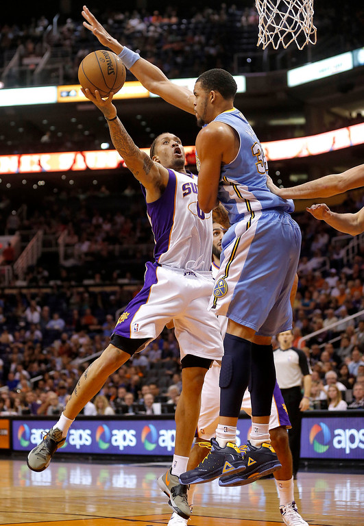 . Phoenix Suns\' Michael Beasley shoots under Denver Nuggets\' JaVale McGee, right, during the second half of an NBA basketball game, Monday, March 11, 2013, in Phoenix.  (AP Photo/Matt York)