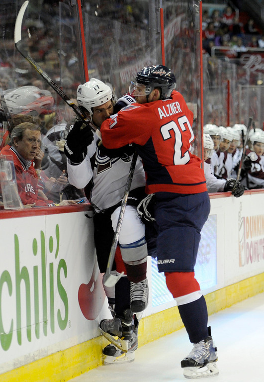 . Washington Capitals defenseman Karl Alzner (27) checks Colorado Avalanche right wing Steve Downie (17) into the boards during the second period an NHL hockey game, Saturday, Oct. 12, 2013, in Washington. (AP Photo/Nick Wass)