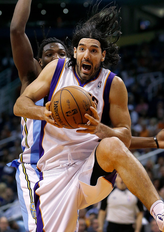 . Phoenix Suns\' Luis Scola, of Argentina, pulls down a rebound against the Denver Nuggets during the second half of an NBA basketball game, Monday, March 11, 2013, in Phoenix. (AP Photo/Matt York)