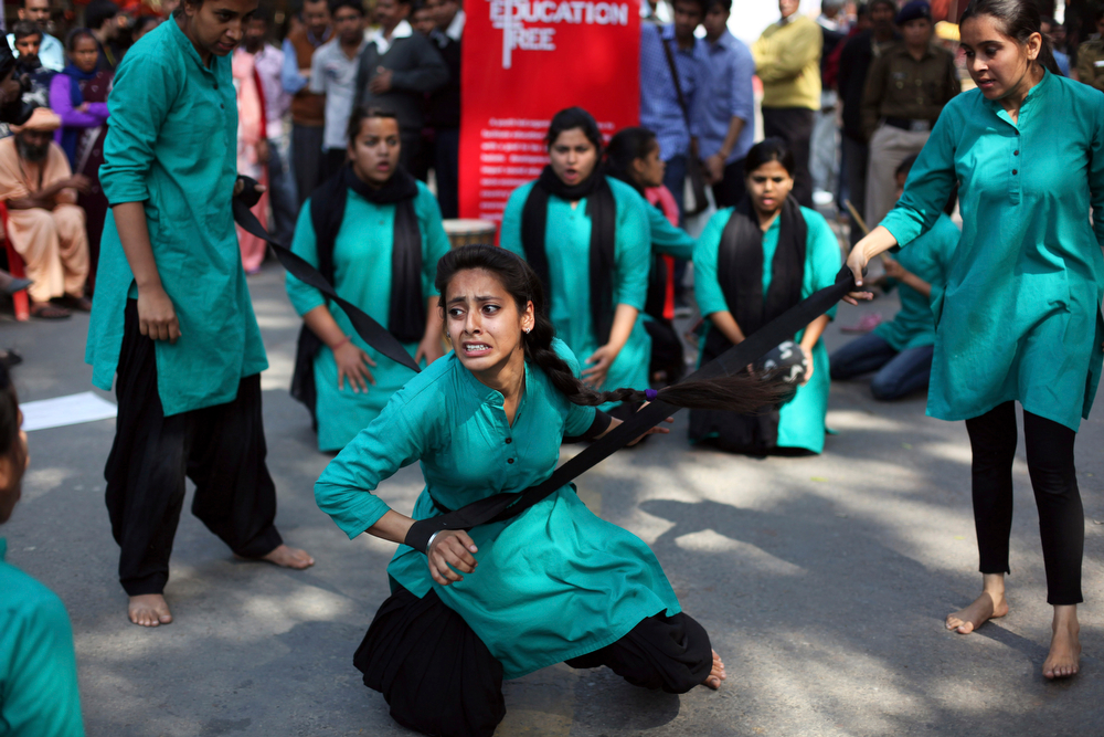 Description of . A group of college girls perform a street play on violence against women, to mark International Women's Day in New Delhi, India, Saturday, March 8, 2014. (AP Photo/Tsering Topgyal)