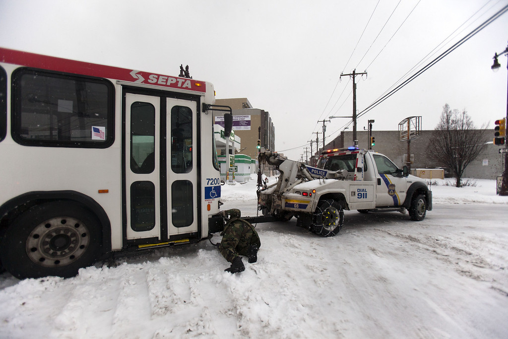 . Police work to tow away a Septa bus that slid off the road on February 13, 2014 in Philadelphia, Pennsylvania. The east coast was hit with a winter snowstorm bringing sleet and snow. (Photo by Jessica Kourkounis/Getty Images)