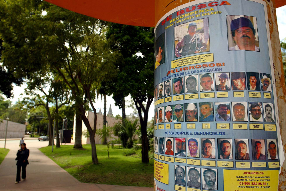 """. A reward poster hangs on a pole at the Revolution Park, Tuesday, March 1, 2005, in Guadalajara, Mexico. The mystery surrounding the posters offering up to US$5 million for information leading to Joaquin \""""El Chapo\"""" Guzman, one of Mexico\'s most poweful drug lords, and 36 of his associates, has intensified after Mexican authorities denied plastering them in three of the country\'s major cities. The Attorney General\'s office said it has opened an investigation to determine who distributed the posters, while Mexican media suggests they are part of a plan by Guzman\'s rivals to get to him. (AP Photo/Guillermo Arias)"""