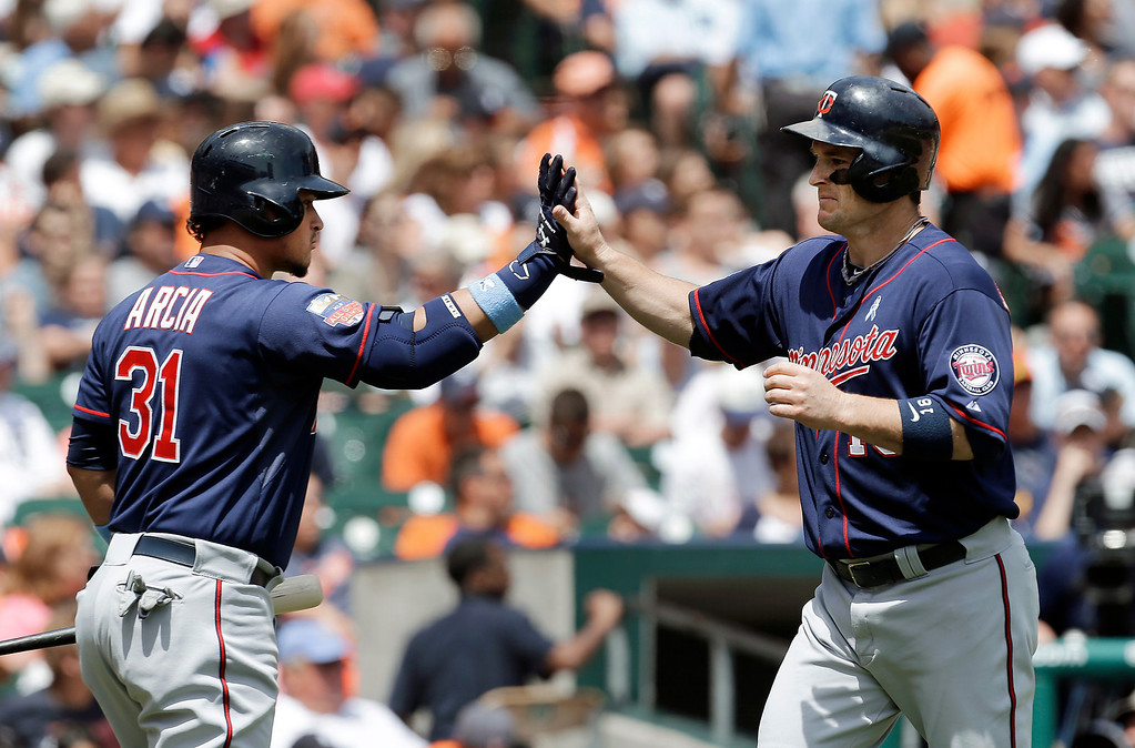 . Minnesota Twins\' Josh Willingham, right, is congratulated by Oswaldo Arcia (31) after scoring on a Kendrys Morales single in the sixth inning of a baseball game against the Detroit Tigers in Detroit, Sunday, June 15, 2014. (AP Photo/Paul Sancya)