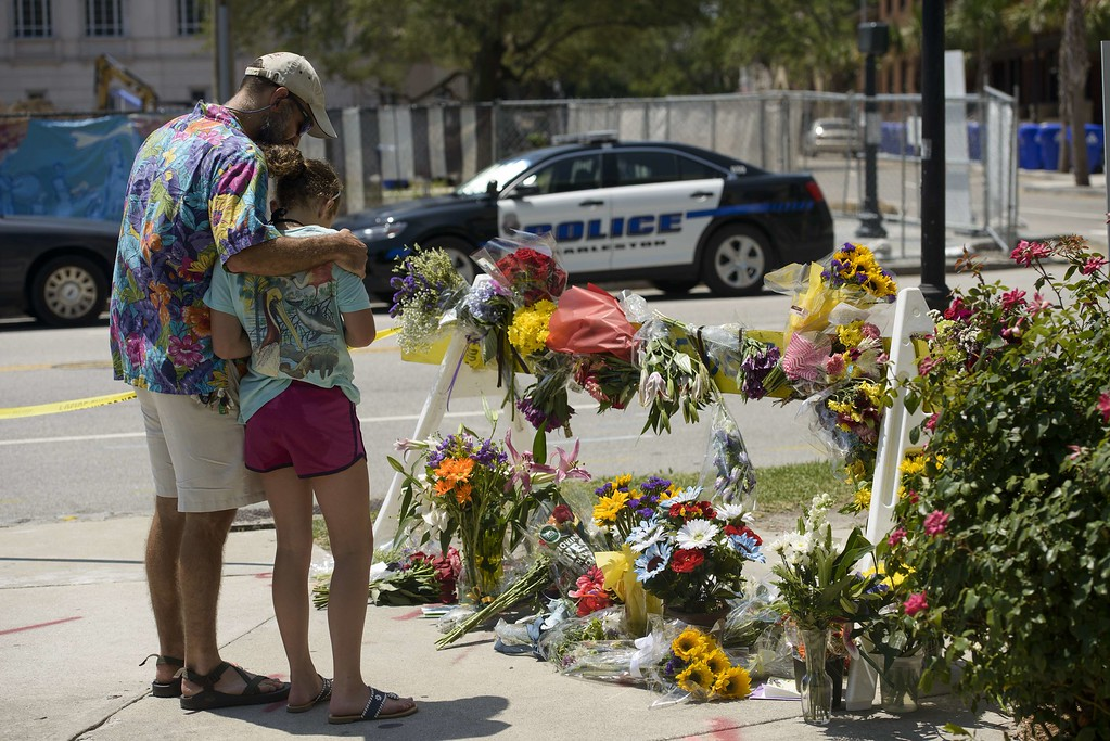 . People visit a makeshift memorial near the Emanuel AME Church June 18, 2015 in Charleston, South Carolina, after a mass shooting at the  Church on the evening of June 17, 2015.  US police on Thursday arrested a 21-year-old white gunman suspected of killing nine people at a prayer meeting in one of the nation\'s oldest black churches in Charleston, an attack being probed as a hate crime. The shooting at the Emanuel African Methodist Episcopal Church in the southeastern US city was one of the worst attacks on a place of worship in the country in recent years, and comes at a time of lingering racial tensions. AFP PHOTO/BRENDAN SMIALOWSKI/AFP/Getty Images
