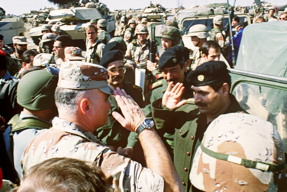Description of . US Commander General Norman Schwarzkopf (L) salutes Iraqi Lt. General Sultan Hasheem Ahmad at the end of their talks, 03 March 1991, at a captured Iraqi desert air-base to set cease-fire terms in the Persian Gulf war. (MIKE NELSON/AFP/Getty Images)