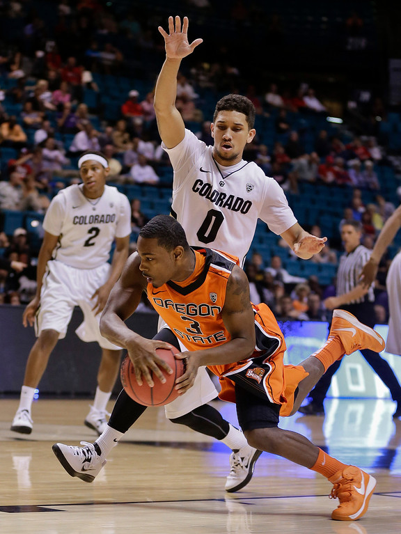 . Oregon State\'s Ahmad Starks (3) is fouled by Colorado\'s Askia Booker (0) as he drives to the basket in the first half of a Pac-12 tournament NCAA college basketball game, Wednesday, March 13, 2013, in Las Vegas. (AP Photo/Julie Jacobson)