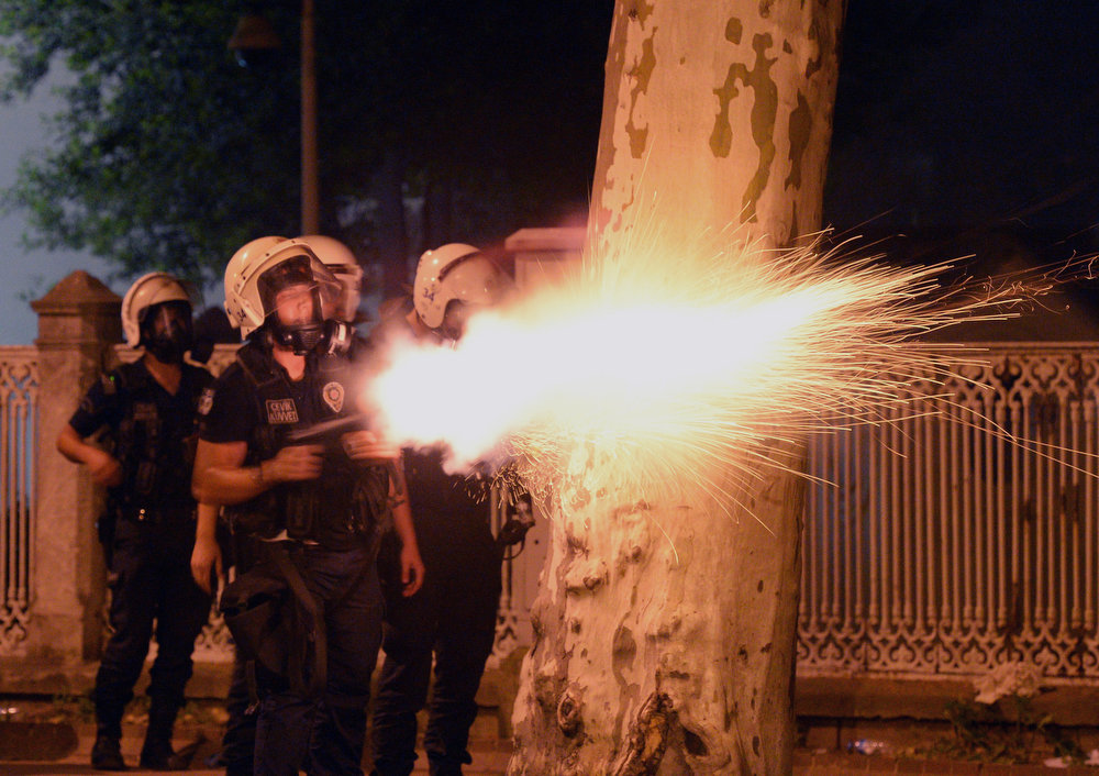 . In this photo taken late Saturday, June 1, 2013, riot police fire, as they clash with protestors, near the former Ottoman palace, Dolmabahce, where Turkey\'s Prime Minister Recep Tayyip Erdogan maintains an office in Istanbul, Turkey. Protests in Istanbul, Ankara and several other Turkish cities appear to have subsided Sunday, after days of fierce clashes following a police crackdown on a peaceful gathering as protesters denounced what they see as Prime Minister Recep Tayyip Erdogan\'s increasingly authoritarian style. (AP Photo)