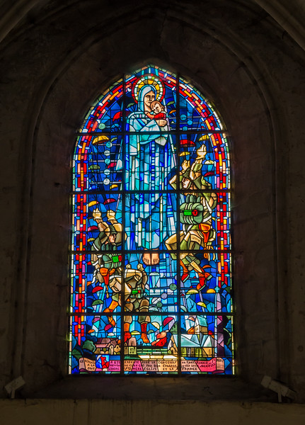 """This window depicts the Virgin Mary and Child above a burning Sainte Mere Eglise with paratroopers and planes around her.  Inscription:  """"This stained glass was completed with the participation of Paul Renaud and Sainte Mere, for the memory of those who, with their courage and sacrifice, liberated Sainte Mere Eglise and France."""""""