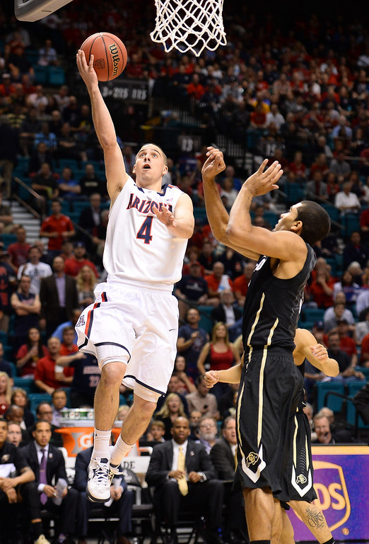 . LAS VEGAS, NV - MARCH 14:  T.J. McConnell #4 of the Arizona Wildcats shoots against Xavier Talton #3 of the Colorado Buffaloes during a semifinal game of the Pac-12 Basketball Tournament at the MGM Grand Garden Arena on March 14, 2014 in Las Vegas, Nevada. Arizona won 63-43.  (Photo by Ethan Miller/Getty Images)