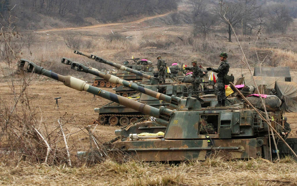 . South Korean marines stand on their K-55 self-propelled howitzers during an exercise against possible attacks by North Korea near the border village of Panmunjom in Paju, South Korea  Monday, April 1, 2013.  After weeks of war-like rhetoric, North Korean leader Kim Jong Un gathered legislators Monday for an annual spring parliamentary session taking place one day after top party officials adopted a statement declaring building nuclear weapons and the economy the nation\'s top priorities.(AP Photo/Ahn Young-joon)
