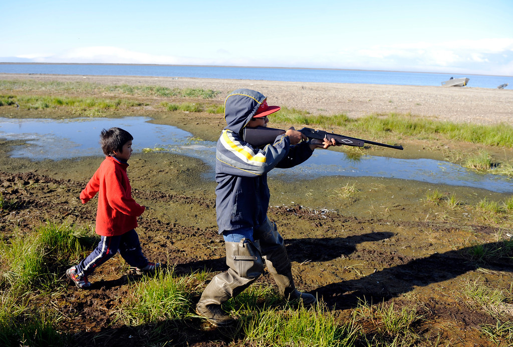 . Point Hope Alaska native, Aldred Omnik, 12-years-old, right, uses a bb-gun to try and shoot small birds practicing his hunting skills with Jolian Lane, left, 7-years-old, in tow along the north side of the village Monday afternoon, July 26th 2010.  Point Hope Alaska, population of 800 people, is  located along the Chukchi Sea coast of the Arctic Ocean. The village lives a mostly subsistence life of hunting whales, seal, caribou, walrus, salmon fish and many other species and have for thousands of years. The Denver Post/Andy Cross