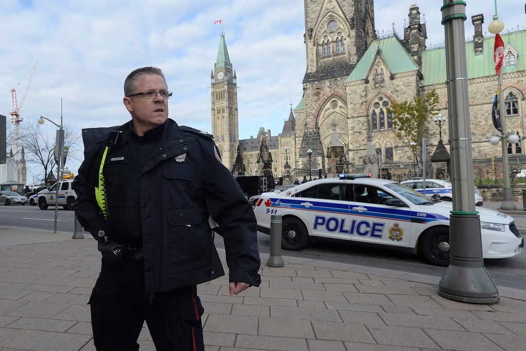 . A police officer secures the scene of a shooting on Parliament Hill in Ottawa on Wednesday Oct. 22, 2014.  A soldier standing guard at the National War Memorial in Ottawa has been shot by an unknown gunman and people report hearing gunfire inside the halls of Parliament.  The gunman reportedly ran towards Parliament Hill, which is currently under lockdown and surrounded by security.  Prime Minister Stephen Harper was rushed away from the building to an undisclosed location, officials in his office said. (AP Photo/The Canadian Press, Adrian Wyld)
