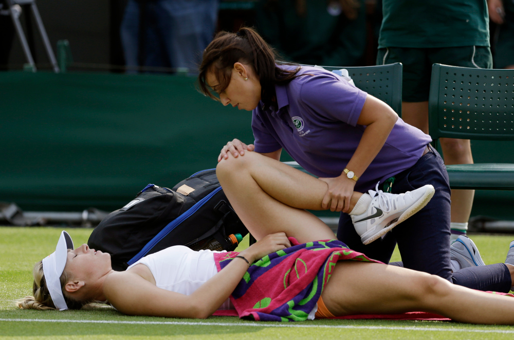 . Maria Sharapova of Russia is attended to by a physiotherapist during her Women\'s second round singles match against Michelle Larcher De Brito of Portugal at the All England Lawn Tennis Championships in Wimbledon, London, Wednesday, June 26, 2013. (AP Photo/Anja Niedringhaus)