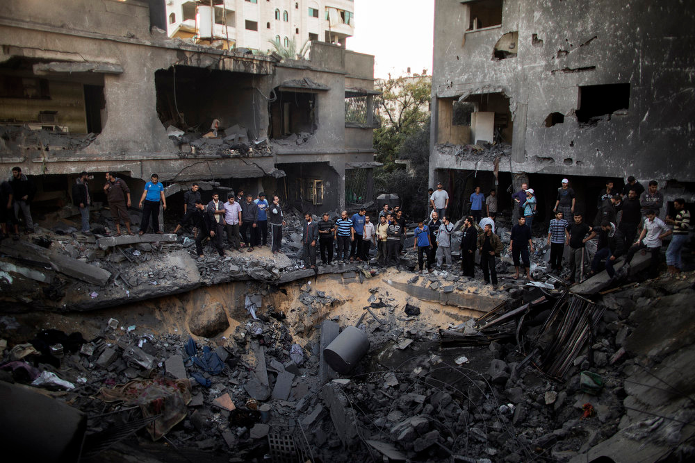 Description of . Palestinian men gather around a crater caused by an Israeli air strike on the al-Dallu family's home in Gaza City on November 18, 2012. Israeli air strikes killed at least 18 Palestinians in the bloodiest day so far of its massive air campaign on the Gaza Strip, as diplomatic efforts to broker a truce intensified. MARCO LONGARI/AFP/Getty Images
