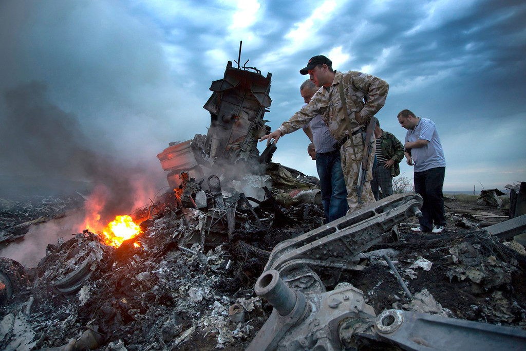 . People inspect the crash site of a passenger plane near the village of Grabovo, Ukraine, Thursday, July 17, 2014. Ukraine said a passenger plane carrying 295 people was shot down Thursday as it flew over the country, and both the government and the pro-Russia separatists fighting in the region denied any responsibility for downing the plane. (AP Photo/Dmitry Lovetsky)