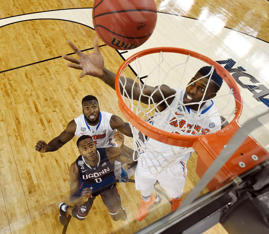 . Florida forward Casey Prather shoots as Connecticut forward Phillip Nolan (0) and Florida\'s Patric Young (4) look on during the first half of an NCAA Final Four tournament college basketball semifinal Saturday, April 5, 2014, in Arlington, Texas. (AP Photo/Chris Steppig, Pool)