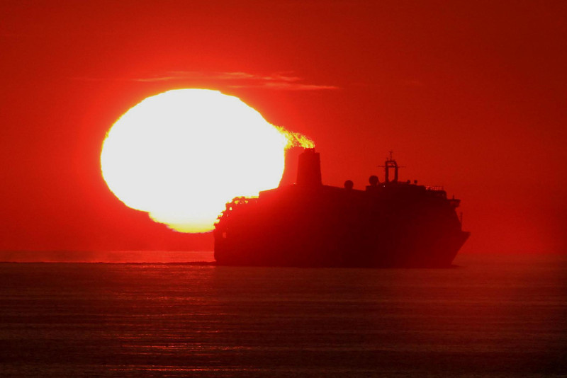 "The cruise ship Aurora, a P&O vessel shown here, shadowed us much of the way to Norway from England. The sunset  ""fireball"" effect out of the smokestack only lasted a few seconds but I was able to click off a shot before it went away. This is a cropped 400 MM image, f11 at 1/1000 second."