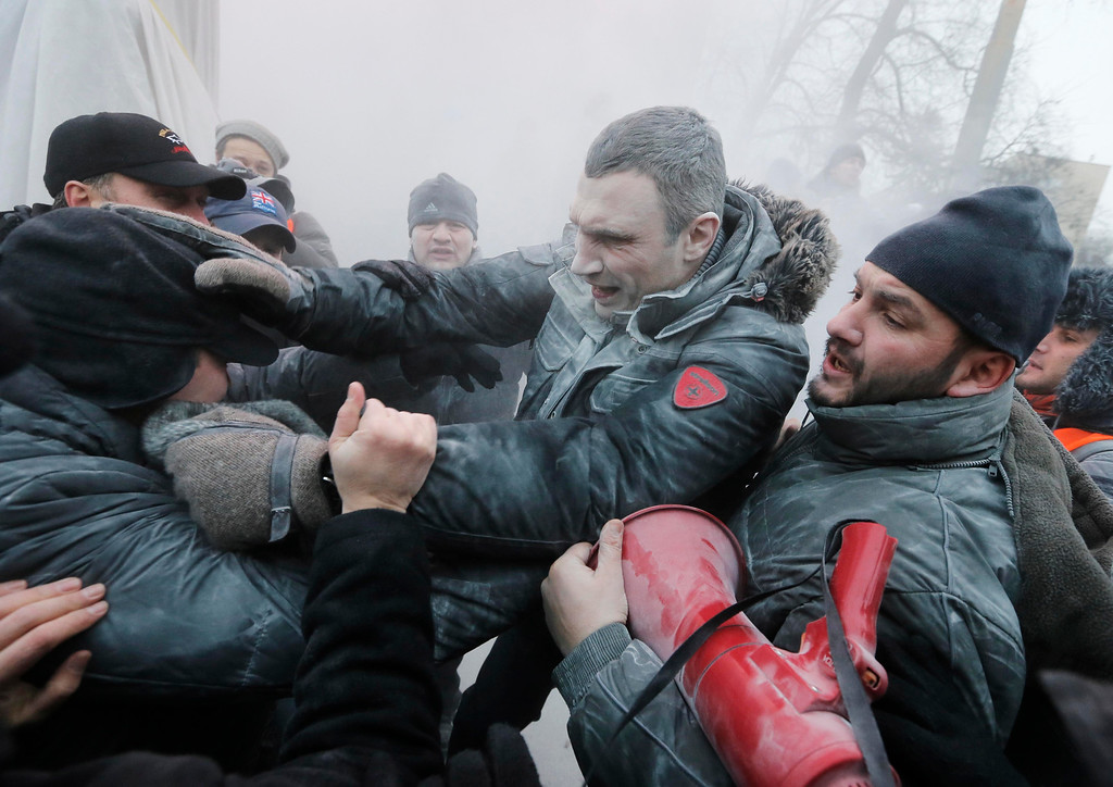 . Opposition leader and former WBC heavyweight boxing champion Vitali Klitschko, center, is attacked and sprayed with a fire extinguisher as he tries to stop the clashes between police and protesters  in central Kiev, Ukraine, Sunday, Jan. 19, 2014. (AP Photo/Efrem Lukatsky, File)