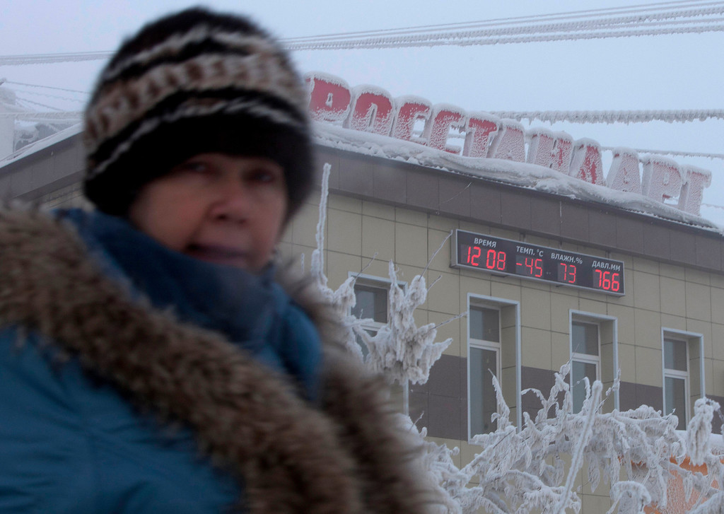 . A woman passes a board on a building, displaying the local time, temperature, humidity and air pressure in Yakutsk, in the Republic of Sakha, northeast Russia, January 17, 2013. The coldest temperatures in the northern hemisphere have been recorded in Sakha, the location of the Oymyakon valley, where according to the United Kingdom Met Office a temperature of -67.8 degrees Celsius (-90 degrees Fahrenheit) was registered in 1933 - the coldest on record in the northern hemisphere since the beginning of the 20th century. Yet despite the harsh climate, people live in the valley, and the area is equipped with schools, a post office, a bank, and even an airport runway (albeit open only in the summer). Picture taken January 17, 2013.    REUTERS/Maxim Shemetov