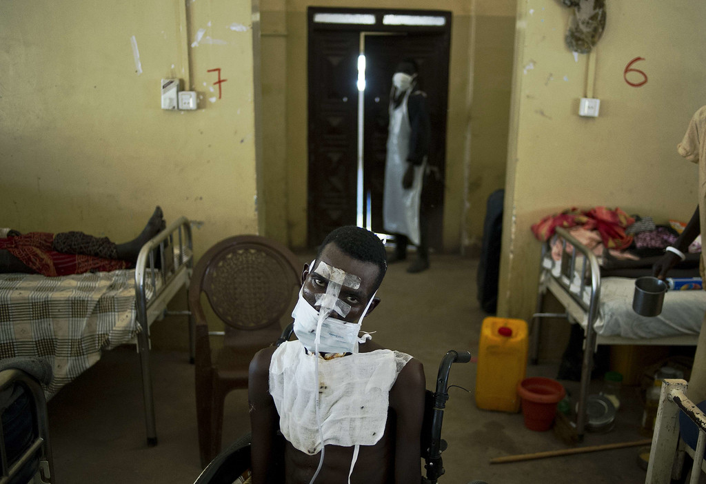 . A patient being treated for multiple gunshot wounds to the face, chest and throat sits in a wheelchair in the Malakal teaching hospital on February 5, 2014.  AFP PHOTO / CARL DE SOUZA/AFP/Getty Images