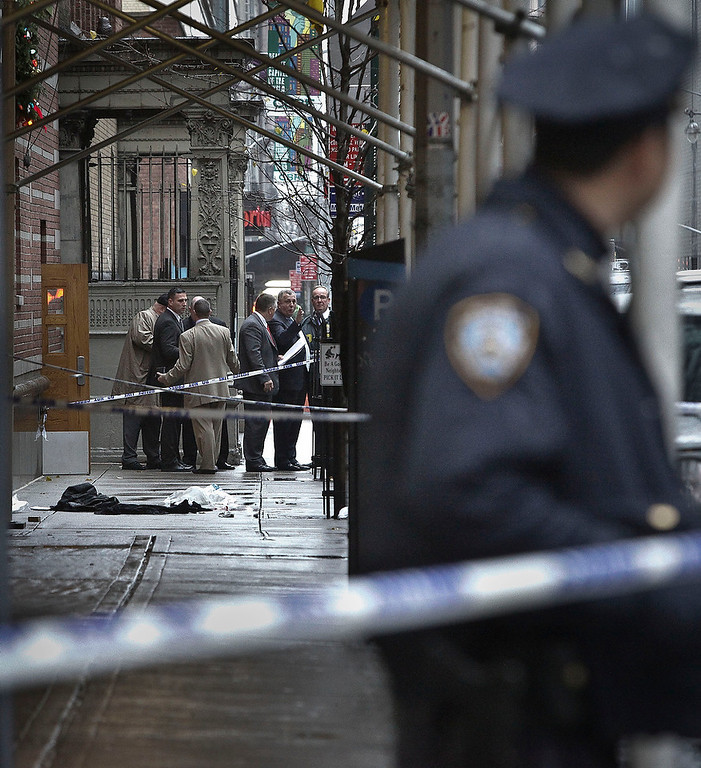 . Police investigate the scene where a man was fatally shot in the back of the head in New York on Monday, Dec. 10, 2012. Authorities said the man was shot outside a school near Columbus Circle in Manhattan, lying mortally wounded in a pool of blood as the suspect escaped with a getaway driver. (AP Photo/Bebeto Matthews)