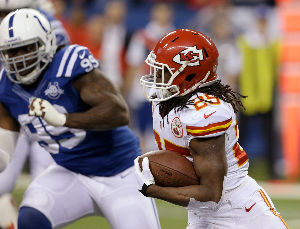 . Kansas City Chiefs running back Jamaal Charles (25) runs as Indianapolis Colts defensive end Ricky Jean Francois (99) moves in during the first half of an NFL wild-card playoff football game Saturday, Jan. 4, 2014, in Indianapolis. (AP Photo/Darron Cummings)