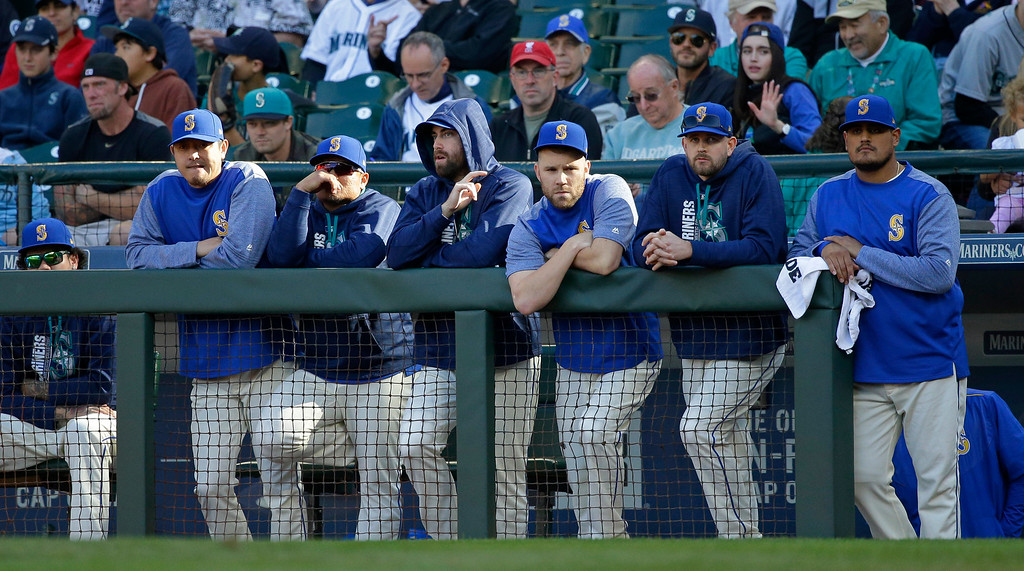 . Seattle Mariners players stand at the dugout rail during the ninth inning of a baseball game against the Cleveland Indians, Sunday, Sept. 24, 2017, in Seattle. The Mariners were eliminated from post-season play as the Indians won 4-2. (AP Photo/Ted S. Warren)