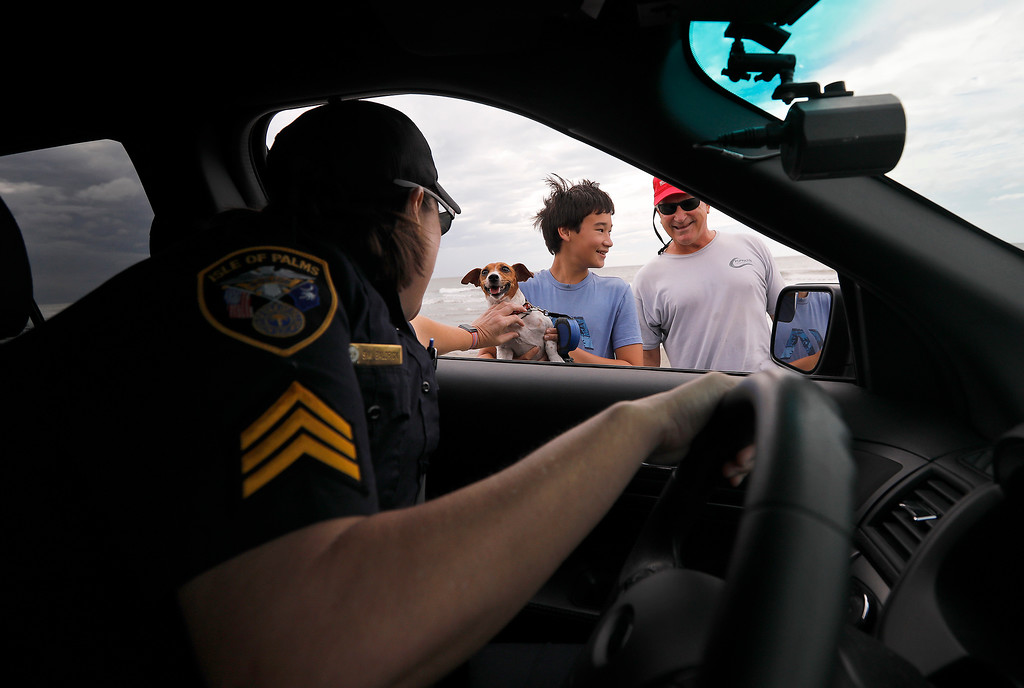 . Isle of Palms police officer Detective Sergeant Sharon Baldrick speaks with Isle of Palms residents James Sireci, at right, and his son Aaron as she pets their family dog, Allie, on the Isle of Palms, S.C., as Hurricane Florence moves ashore near Wilmington, N.C., Friday, Sept. 14, 2018. (AP Photo/Mic Smith)