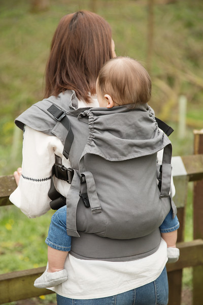 Izmi_Toddler_Carrier_Cotton_Mid_Grey_Lifestyle_Back_Carry_Mum_At_Fence_Portrait.jpg