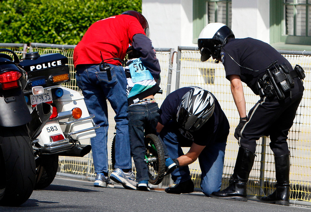 . A riders gets help untangling his shoelace during the public race portion of the Redlands Bicycle Classic on Saturday, April 5, 2014 in Redlands, Ca. (Photo by Micah Escamilla for the Redlands Daily Facts)