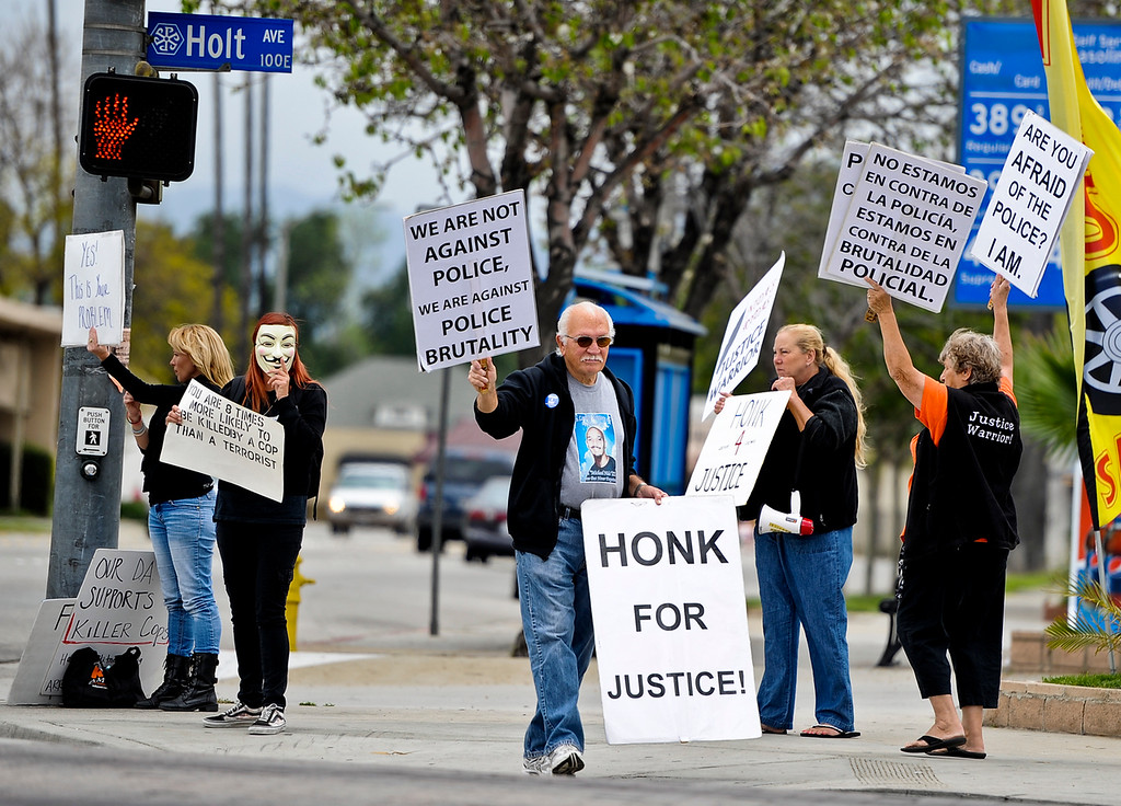 . Family members of Andres Avila and their supporters gather to protest the October 2011 police-involved shooting of Avila at the intersection of Garey and Holt Avenues in Pomona on Sunday, April 14, 2013. The group held signs against police corruption and marched to the Pomona police station. (Rachel Luna / Staff Photographer)