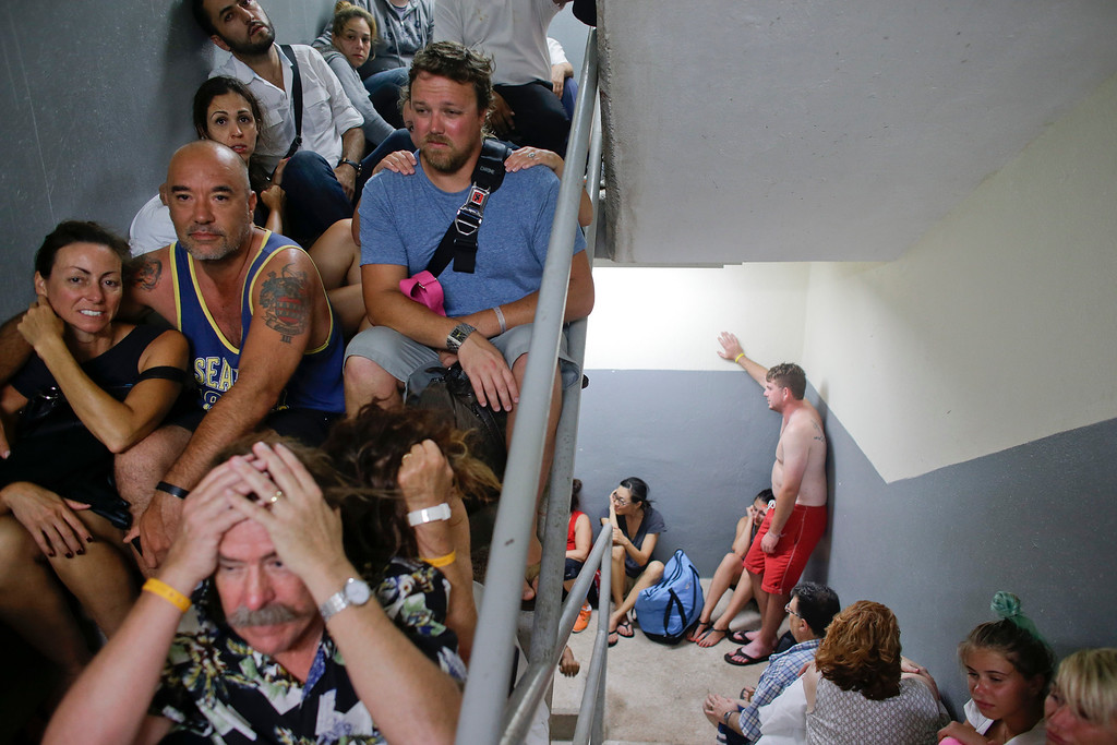 . Tourists sit on the concrete stairs in the service area of a resort after the designated area for shelter was destroyed by winds in Los Cabos, Mexico,  Monday, Sept. 15, 2014. Hurricane Odile raked the Baja California Peninsula with strong winds and heavy rains early Monday as locals and tourists in the resort area of Los Cabos began to emerge from shelters and assess the damage. (AP Photo/Victor R. Caivano)