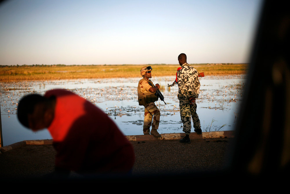 . A French soldier speaks with his Malian counterpart on the banks of the Niger river outside Gao, northern Mali, Thursday, Feb. 7, 2013. French troops began to withdraw from Timbuktu Thursday after securing the fabled city as they ramped up their mission in another northern Mali city, searching for Islamic extremists who may be mixing among the local population. (AP Photo/Jerome Delay)