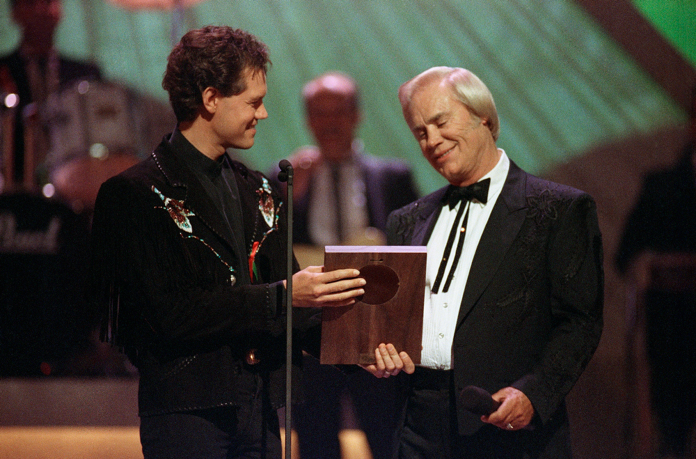 ". FILE - In this Sept. 30, 1992 file photo, Country music legend George Jones accepts his Country Music Hall of Fame award from Randy Travis, left, during the Country Music Association Awards show, Nashville, Tenn. Jones, the peerless, hard-living country singer who recorded dozens of hits about good times and regrets and peaked with the heartbreaking classic ""He Stopped Loving Her Today,\"" has died. He was 81. Jones died Friday, April 26, 2013 at Vanderbilt University Medical Center in Nashville after being hospitalized with fever and irregular blood pressure, according to his publicist Kirt Webster. (AP Photo/Mark Humphrey, file)"