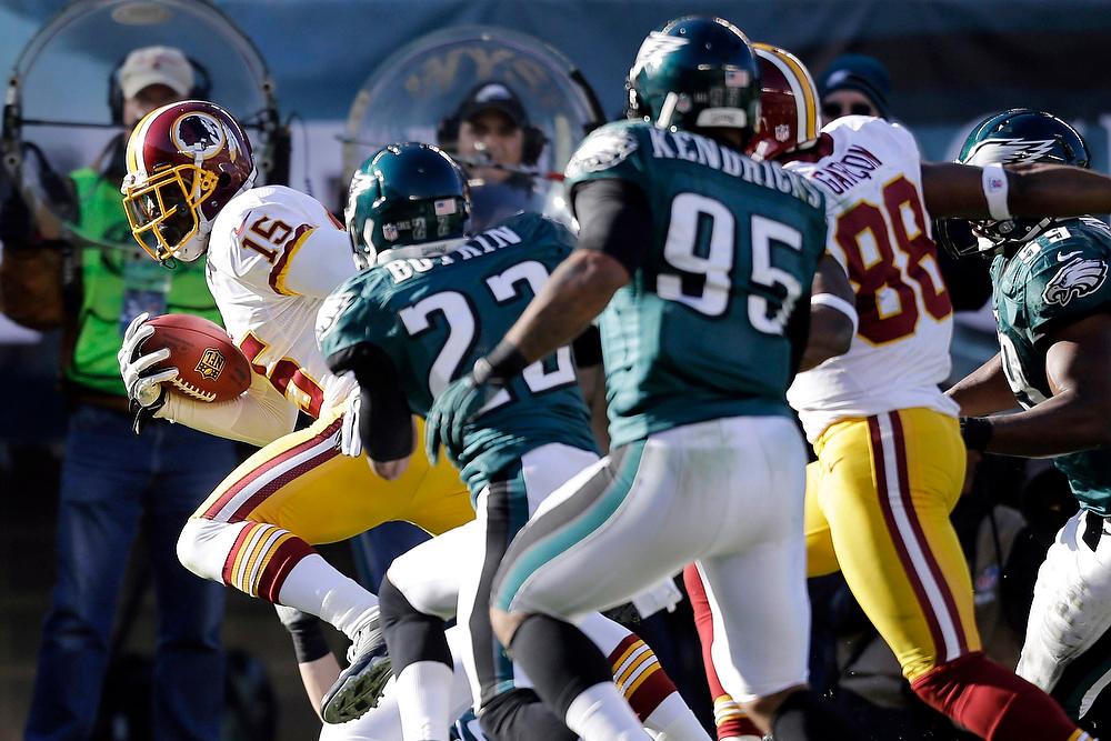 . Washington Redskins\' Josh Morgan, left, runs for a touchdown past Philadelphia Eagles\' Brandon Boykin and Mychal Kendricks in the first half of an NFL football game, Sunday, Dec. 23, 2012, in Philadelphia. (AP Photo/Mel Evans)