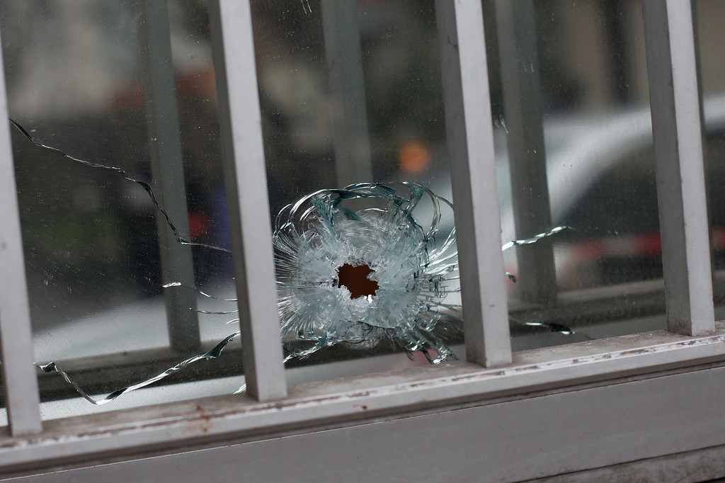 ". A bullet impact is seen in a window of a building next to the French satirical newspaper Charlie Hebdo\'s office, in Paris, Wednesday, Jan. 7, 2015.  Masked gunmen shouting ""Allahu akbar!\"" stormed the Paris offices of a satirical newspaper Wednesday, killing at least 12 people, including the paper\'s editor, before escaping in a getaway car.  (AP Photo/Thibault Camus)"