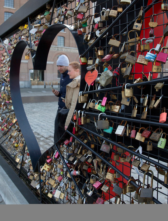 . A couple stop to look at locks placed on a fence next to a metal heart in Antwerp, Belgium, on Tuesday, Feb. 14, 2017.  The city of Antwerp provided the fence for couples to place their symbolic locks for Valentine\'s Day. (AP Photo/Virginia Mayo)