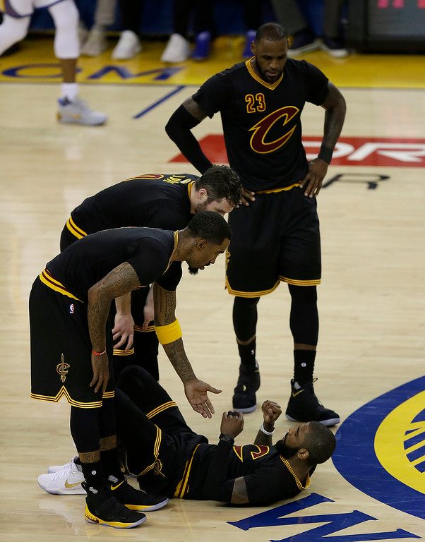 . Cleveland Cavaliers guard Kyrie Irving, bottom, is helped up by teammates during the first half of Game 2 of basketball\'s NBA Finals against the Golden State Warriors in Oakland, Calif., Sunday, June 4, 2017. (AP Photo/Ben Margot)