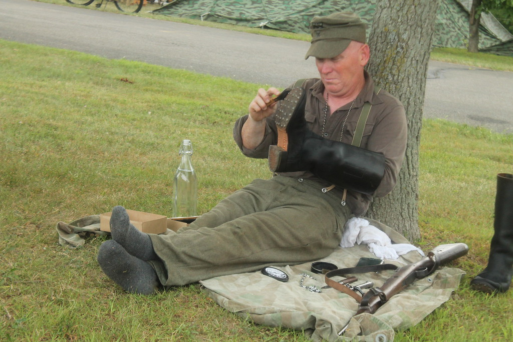 . David Arsenault  German solider renenactor cleans his boots his boots and gun during  D-Day Conneaut 2018 . Kristi Garabrandt - The News-Herald