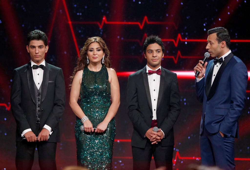 ". The three finalists (L - R) Palestinian Mohammed Assaf, Syrian Farah Yousef and Egyptian Ahmed Jamal wait for the results as they stand on stage during the Season 2 finale of ""Arab Idol\"" in Zouk Mosbeh area, north of Beirut June 22, 2013.  REUTERS/Mohammed Azakir"