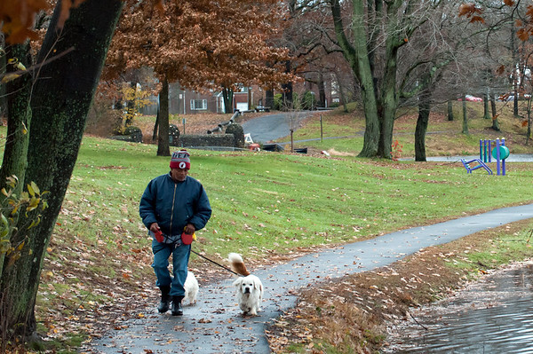 11/13/18 Wesley Bunnell | Staff Mario Cortes walks his dogs Brownie and Fluffy through a cold and wet Stanley Quarter Park on Tuesday afternoon.