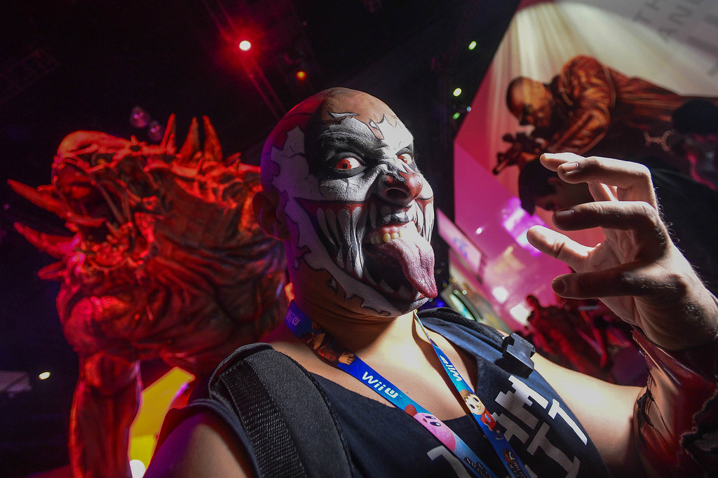". Karcamo stands before a monster character from the video game ""Evolve\"" during Electronic Entertainment Expo in Los Angeles on Tuesday, June 10, 2014. (Photo by Watchara Phomicinda)"