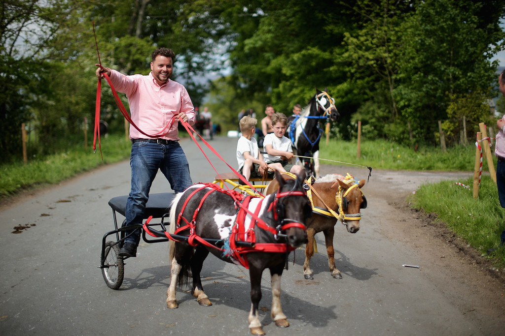 . Travelers race their horses along the \'Mad Mile\' during the Appleby Horse Fair on June 4, 2015 in Appleby, England. The Appleby Horse Fair has existed under the protection of a charter granted by James II since 1685 and is one of the key gathering points for the Romany, gypsy and traveling community. The fair is attended by about 5,000 travelers who come to buy and sell horses. The animals are washed and groomed before being ridden at high speed along the \'mad mile\' for the viewing of potential buyers.  (Photo by Christopher Furlong/Getty Images)