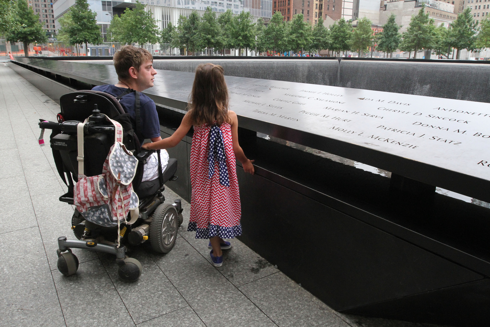 Description of . Retired Marine Corps Sgt. John Peck, of Fredricksburg, Va., left, and Sophia Elwood, 7, the daughter of Peck's fiancee, pause beside the south reflecting pool at the 9/11 Memorial in New York, Friday, July 4, 2014, during an event honoring those that lost their lives on 9/11 and those who survived. Peck, who is a quadruple amputee as a result of an incident during his service in Afghanistan, was one of a group of severly injured servicemen who served in Afghanistan and/or Iraq who took part in the event.  (AP Photo/Tina Fineberg)