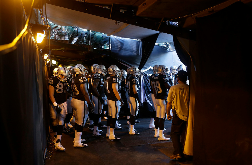 . Oakland Raiders players wait in the tunnel before entering the field before an NFL preseason football game against the Detroit Lions in Oakland, Calif., Friday, Aug. 15, 2014. (AP Photo/Jeff Chiu)