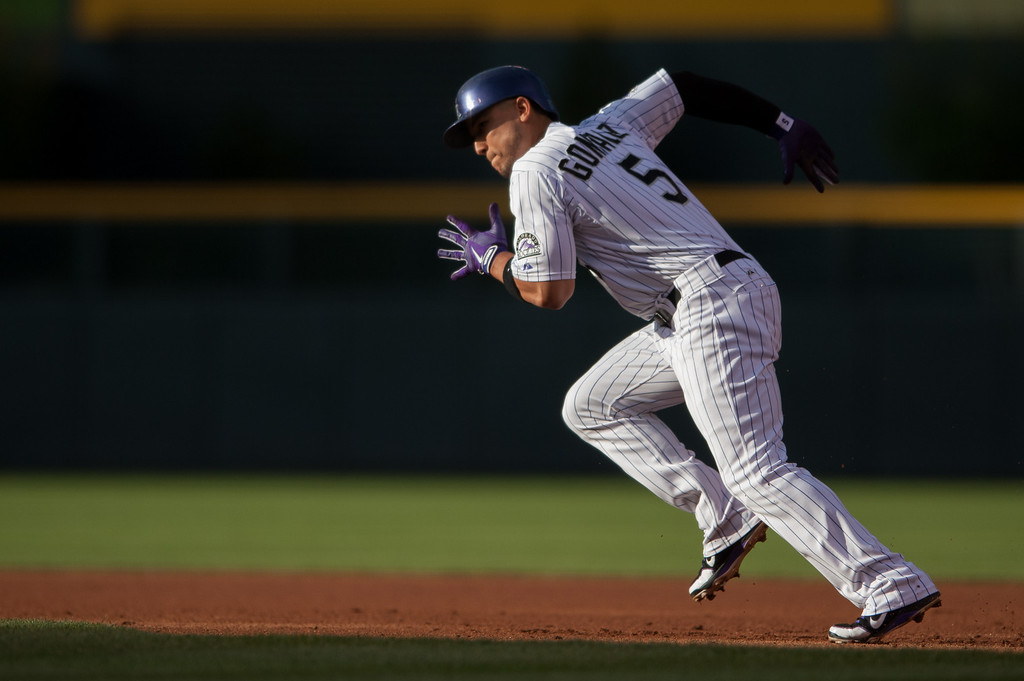 . DENVER, CO - JULY 24:  Carlos Gonzalez #5 of the Colorado Rockies takes off towards second base on a steal attempt in the first inning of a game against the Miami Marlins at Coors Field on July 24, 2013 in Denver, Colorado. Gonzalez was thrown out at second base.  (Photo by Dustin Bradford/Getty Images)